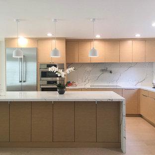 Modern inredning av ett stort vit vitt kök, med en undermonterad diskho, släta luckor, beige skåp, bänkskiva i kvarts, vitt stänkskydd, stänkskydd i sten, rostfria vitvaror, ljust trägolv, en köksö och beiget golv