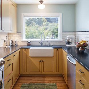 Inredning av ett klassiskt avskilt, litet u-kök, med en rustik diskho, skåp i shakerstil, gula skåp, bänkskiva i täljsten, vitt stänkskydd, stänkskydd i tunnelbanekakel, rostfria vitvaror och ljust trägolv