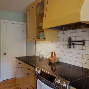 Exempel på ett avskilt, litet klassiskt u-kök, med en rustik diskho, skåp i shakerstil, gula skåp, bänkskiva i täljsten, vitt stänkskydd, stänkskydd i tunnelbanekakel, rostfria vitvaror och ljust trägolv