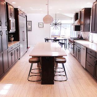 Zweizeilige, Große Moderne Wohnküche mit Unterbauwaschbecken, Schrankfronten mit vertiefter Füllung, schwarzen Schränken, Küchenrückwand in Weiß, Küchengeräten aus Edelstahl, hellem Holzboden und Kücheninsel in Sonstige