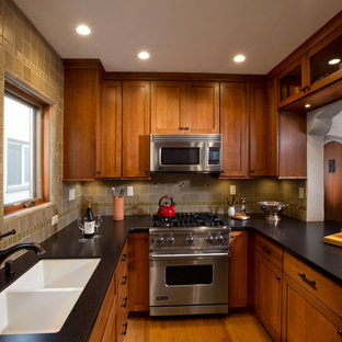 Design ideas for a small arts and crafts u-shaped eat-in kitchen in Los Angeles with a double-bowl sink, shaker cabinets, medium wood cabinets, granite benchtops, green splashback, ceramic splashback, stainless steel appliances, medium hardwood floors, a peninsula, brown floor and black benchtop.
