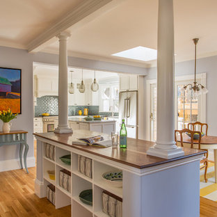 Photo of a large victorian l-shaped eat-in kitchen in Boston with a farmhouse sink, shaker cabinets, white cabinets, marble benchtops, blue splashback, glass tile splashback, stainless steel appliances, medium hardwood floors and multiple islands.