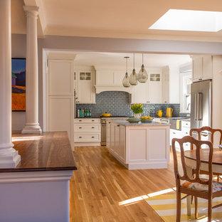 Cette image montre une grande cuisine américaine victorienne en L avec un évier de ferme, un placard à porte shaker, des portes de placard blanches, un plan de travail en marbre, une crédence en carreau de verre, un électroménager en acier inoxydable, un sol en bois brun, une crédence bleue et 2 îlots.
