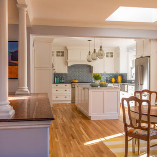 Design ideas for a large victorian l-shaped eat-in kitchen in Boston with a farmhouse sink, shaker cabinets, white cabinets, marble benchtops, glass tile splashback, stainless steel appliances, medium hardwood floors, blue splashback and multiple islands.