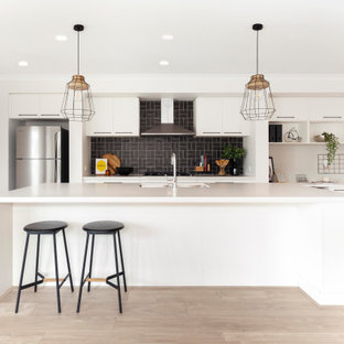 Inspiration for a contemporary galley open plan kitchen in Melbourne with an undermount sink, white cabinets, quartz benchtops, ceramic splashback, stainless steel appliances, laminate floors, with island, beige floor, white benchtop, flat-panel cabinets and black splashback.
