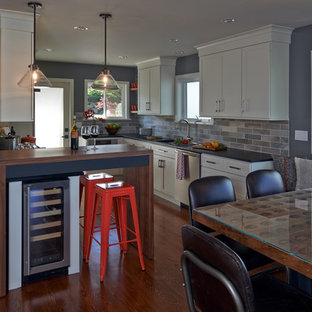 Mid-sized midcentury galley eat-in kitchen in Seattle with shaker cabinets, white cabinets, soapstone benchtops, green splashback, stainless steel appliances, medium hardwood floors, a farmhouse sink, slate splashback, with island and brown floor.