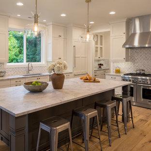シアトルの中くらいのトランジショナルスタイルのおしゃれなキッチン (アンダーカウンターシンク、シェーカースタイル扉のキャビネット、白いキャビネット、パネルと同色の調理設備、無垢フローリング、大理石カウンター、マルチカラーのキッチンパネル、テラコッタタイルのキッチンパネル) の写真