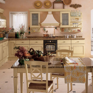 Photo of a mid-sized country l-shaped eat-in kitchen in New York with an undermount sink, raised-panel cabinets, distressed cabinets, tile benchtops, ceramic floors, no island and beige floor.