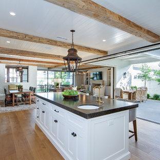 オレンジカウンティの広いカントリー風おしゃれなキッチン (エプロンフロントシンク、シェーカースタイル扉のキャビネット、白いキャビネット、珪岩カウンター、ベージュキッチンパネル、セラミックタイルのキッチンパネル、シルバーの調理設備、淡色無垢フローリング、茶色い床、ベージュのキッチンカウンター) の写真