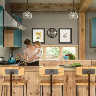Transitional eat-in kitchen ideas - Inspiration for a transitional eat-in kitchen remodel in Portland Maine with flat-panel cabinets, blue cabinets, gray backsplash and a peninsula