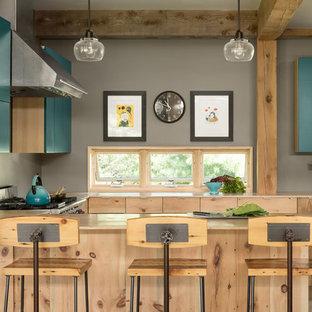 ポートランド(メイン)のカントリー風おしゃれなキッチン (フラットパネル扉のキャビネット、ターコイズのキャビネット、シルバーの調理設備、ベージュのキッチンカウンター) の写真
