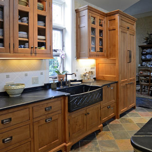 Traditional kitchen remodeling - Example of a classic slate floor kitchen design in Cincinnati with a farmhouse sink