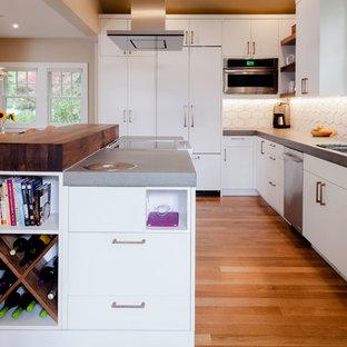 他の地域の中サイズの北欧スタイルのおしゃれなキッチン (アンダーカウンターシンク、フラットパネル扉のキャビネット、白いキャビネット、コンクリートカウンター、白いキッチンパネル、セラミックタイルのキッチンパネル、パネルと同色の調理設備、無垢フローリング、茶色い床、グレーのキッチンカウンター) の写真