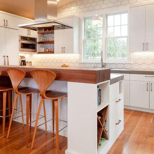 ポートランドの中サイズの北欧スタイルのおしゃれなキッチン (フラットパネル扉のキャビネット、白いキャビネット、コンクリートカウンター、白いキッチンパネル、セラミックタイルのキッチンパネル、パネルと同色の調理設備、無垢フローリング、グレーのキッチンカウンター) の写真