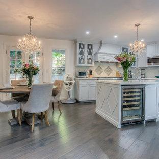 This is an example of a traditional galley open plan kitchen in Los Angeles with shaker cabinets, glass tiled splashback, stainless steel appliances, an island, white cabinets and grey splashback.