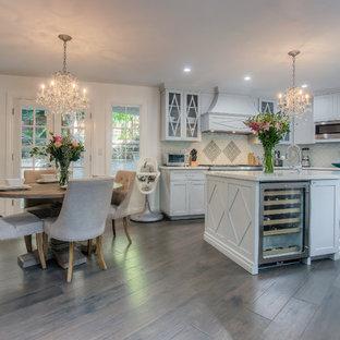 Idées déco pour une cuisine ouverte parallèle classique avec un placard à porte shaker, une crédence en carreau de verre, un électroménager en acier inoxydable, un îlot central, des portes de placard blanches et une crédence grise.