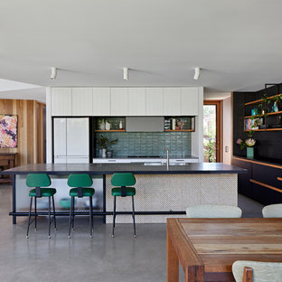 Scandinavian single-wall open plan kitchen in Melbourne with a drop-in sink, flat-panel cabinets, white cabinets, green splashback, white appliances, concrete floors, with island, grey floor and black benchtop.