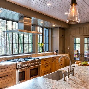他の地域の中くらいのラスティックスタイルのおしゃれなキッチン (落し込みパネル扉のキャビネット、中間色木目調キャビネット、エプロンフロントシンク、シルバーの調理設備、無垢フローリング、御影石カウンター、ベージュキッチンパネル、ガラスまたは窓のキッチンパネル、茶色い床) の写真