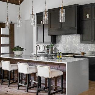 Cette image montre une cuisine design avec un placard à porte shaker, des portes de placard marrons, une crédence blanche, un électroménager en acier inoxydable, un sol en bois clair, un îlot central, un plan de travail blanc, un plafond voûté et un plafond en bois.