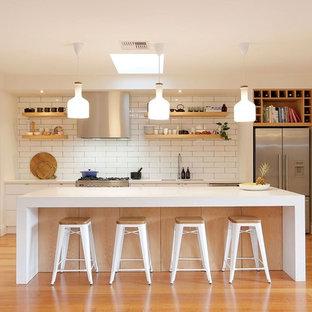 Стильный дизайн: параллельная кухня среднего размера в скандинавском стиле с врезной раковиной, плоскими фасадами, белыми фасадами, белым фартуком, техникой из нержавеющей стали, островом, фартуком из плитки кабанчик и паркетным полом среднего тона - последний тренд