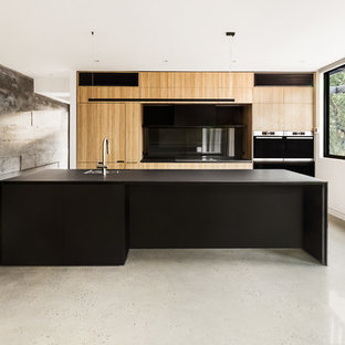 Design ideas for a contemporary kitchen in Melbourne with an undermount sink, glass sheet splashback, black appliances, concrete floors, flat-panel cabinets, light wood cabinets, black splashback and an island.