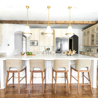 Transitional kitchen pictures - Inspiration for a transitional u-shaped medium tone wood floor, brown floor and exposed beam kitchen remodel in Atlanta with a farmhouse sink, raised-panel cabinets, beige cabinets, multicolored backsplash, stainless steel appliances, an island and multicolored countertops