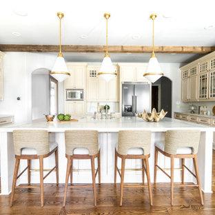 Klassische Küche in U-Form mit Landhausspüle, profilierten Schrankfronten, beigen Schränken, bunter Rückwand, Küchengeräten aus Edelstahl, braunem Holzboden, Kücheninsel, braunem Boden, bunter Arbeitsplatte und freigelegten Dachbalken in Atlanta