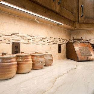 Große Klassische Wohnküche in L-Form mit Landhausspüle, Schrankfronten mit vertiefter Füllung, hellbraunen Holzschränken, bunter Rückwand, Kücheninsel, braunem Boden, Quarzit-Arbeitsplatte, Rückwand aus Travertin, Küchengeräten aus Edelstahl, braunem Holzboden und weißer Arbeitsplatte in Dallas