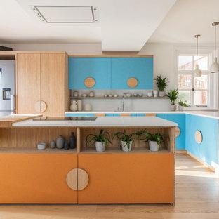 Große Moderne Wohnküche in L-Form mit Waschbecken, flächenbündigen Schrankfronten, orangefarbenen Schränken, Quarzit-Arbeitsplatte, Küchenrückwand in Weiß, Rückwand aus Stein, Küchengeräten aus Edelstahl, braunem Holzboden, Kücheninsel und weißer Arbeitsplatte in Sussex