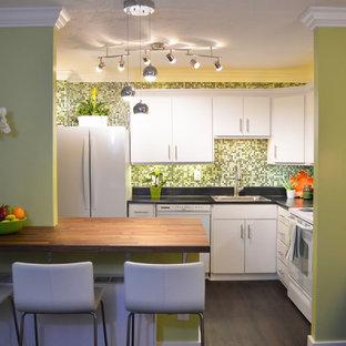 Пример оригинального дизайна: маленькая угловая кухня-гостиная в восточном стиле с накладной раковиной, плоскими фасадами, белыми фасадами, столешницей из ламината, зеленым фартуком, фартуком из стеклянной плитки, белой техникой, полом из винила и островом