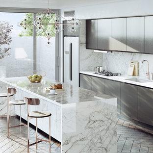 Ejemplo de cocina comedor lineal, actual, con fregadero bajoencimera, armarios con paneles lisos, puertas de armario grises, salpicadero verde, una isla, suelo marrón y encimeras blancas