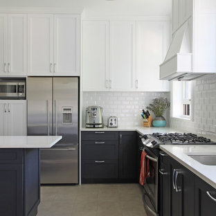 This is an example of a traditional l-shaped kitchen in New York with a submerged sink, shaker cabinets, white cabinets, white splashback, metro tiled splashback and stainless steel appliances.