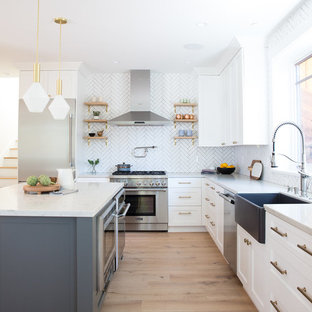 Transitional l-shaped light wood floor and beige floor kitchen photo in San Francisco with a farmhouse sink, shaker cabinets, white cabinets, quartz countertops, white backsplash, stainless steel appliances, an island and white countertops