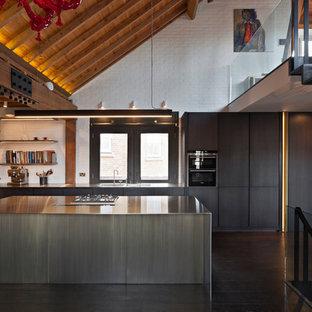 ロンドンのコンテンポラリースタイルのおしゃれなキッチン (フラットパネル扉のキャビネット、黒いキャビネット、ステンレスカウンター、白いキッチンパネル、レンガのキッチンパネル、黒い調理設備、濃色無垢フローリング、茶色い床) の写真