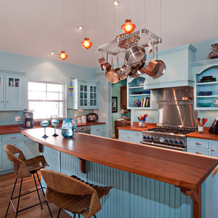 Example of an island style kitchen design in Miami with wood countertops, blue cabinets, shaker cabinets, stainless steel appliances and brown countertops