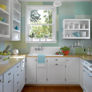 Eclectic kitchen appliance - Eclectic u-shaped medium tone wood floor and orange floor kitchen photo in San Francisco with a drop-in sink, open cabinets, white cabinets, window backsplash and white appliances