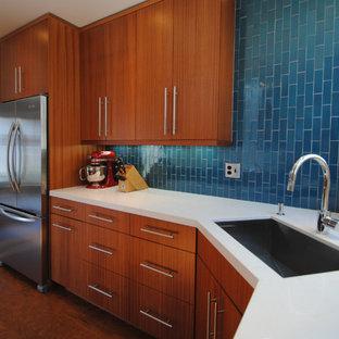 サンフランシスコの中サイズのコンテンポラリースタイルのおしゃれなキッチン (アンダーカウンターシンク、フラットパネル扉のキャビネット、中間色木目調キャビネット、クオーツストーンカウンター、青いキッチンパネル、セラミックタイルのキッチンパネル、シルバーの調理設備の、無垢フローリング、アイランドなし) の写真