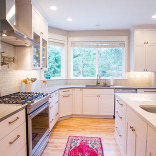 シアトルの中サイズのエクレクティックスタイルのおしゃれなキッチン (アンダーカウンターシンク、落し込みパネル扉のキャビネット、白いキャビネット、クオーツストーンカウンター、白いキッチンパネル、ガラスタイルのキッチンパネル、シルバーの調理設備の、淡色無垢フローリング、ベージュの床、グレーのキッチンカウンター) の写真