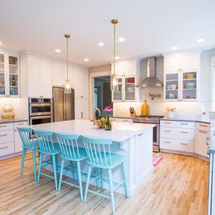 シアトルの中くらいのエクレクティックスタイルのおしゃれなキッチン (アンダーカウンターシンク、落し込みパネル扉のキャビネット、白いキャビネット、クオーツストーンカウンター、白いキッチンパネル、ガラスタイルのキッチンパネル、シルバーの調理設備、淡色無垢フローリング、ベージュの床、グレーのキッチンカウンター) の写真