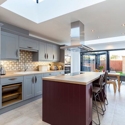 Example of a large transitional single-wall ceramic tile eat-in kitchen design in London with a double-bowl sink, shaker cabinets, blue cabinets, wood countertops, multicolored backsplash, an island, ceramic backsplash and stainless steel appliances