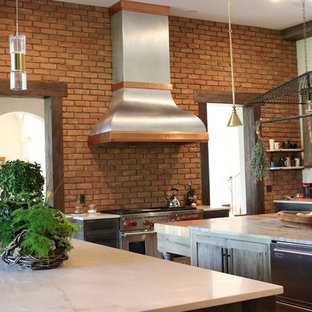 Design ideas for a large contemporary single-wall eat-in kitchen in Atlanta with a farmhouse sink, flat-panel cabinets, distressed cabinets, solid surface benchtops, brown splashback, stone tile splashback, stainless steel appliances, brick floors and multiple islands.