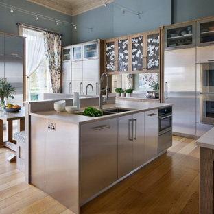 バッキンガムシャーの広いコンテンポラリースタイルのおしゃれなキッチン (ドロップインシンク、ガラス扉のキャビネット、ステンレスキャビネット、珪岩カウンター、ベージュキッチンパネル、シルバーの調理設備、無垢フローリング、ベージュのキッチンカウンター) の写真