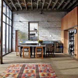 Immagine di una cucina industriale di medie dimensioni con elettrodomestici in acciaio inossidabile, pavimento in legno massello medio e paraspruzzi a effetto metallico