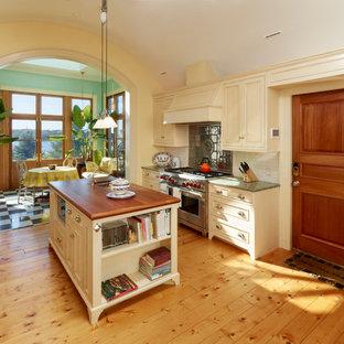 ボストンの中サイズのヴィクトリアン調のおしゃれなキッチン (ドロップインシンク、落し込みパネル扉のキャビネット、ベージュのキャビネット、御影石カウンター、白いキッチンパネル、サブウェイタイルのキッチンパネル、シルバーの調理設備の、淡色無垢フローリング、茶色い床) の写真