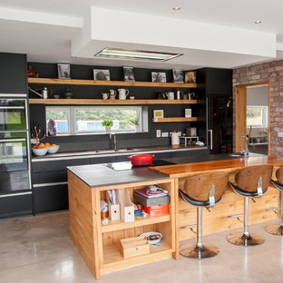 Photo of a large industrial galley open plan kitchen in Cork with a double-bowl sink, flat-panel cabinets, black cabinets, quartzite benchtops, brown splashback, black appliances, concrete floors, with island, grey floor and brown benchtop.