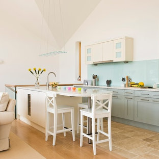 This is an example of a coastal open plan kitchen in Devon with blue splashback, shaker cabinets, blue cabinets, glass sheet splashback, an island, beige floors and beige worktops.