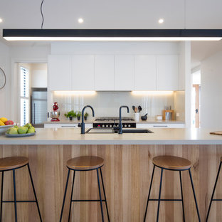 Photo of a large contemporary kitchen in Geelong with an undermount sink, flat-panel cabinets, white cabinets, quartz benchtops, glass sheet splashback, with island, grey splashback and grey benchtop.
