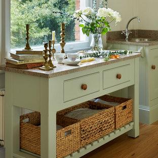 Exempel på ett mellanstort klassiskt kök, med en dubbel diskho, luckor med profilerade fronter, gröna skåp, granitbänkskiva, stänkskydd med metallisk yta, rostfria vitvaror och mellanmörkt trägolv