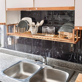 Medium sized eclectic galley kitchen pantry in Toronto with a double-bowl sink, flat-panel cabinets, white cabinets, laminate countertops, black splashback, ceramic splashback, white appliances, medium hardwood flooring, no island, brown floors and grey worktops.