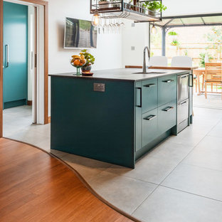 Mid-sized contemporary galley eat-in kitchen in Other with a drop-in sink, turquoise cabinets, quartzite benchtops, metallic splashback, slate splashback, stainless steel appliances, porcelain floors, white floor and multi-coloured benchtop.